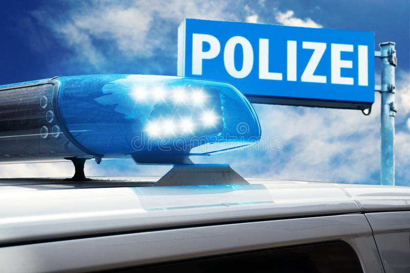 German police car in action. German police car with blue siren against a police sign and blue sky royalty free stock images