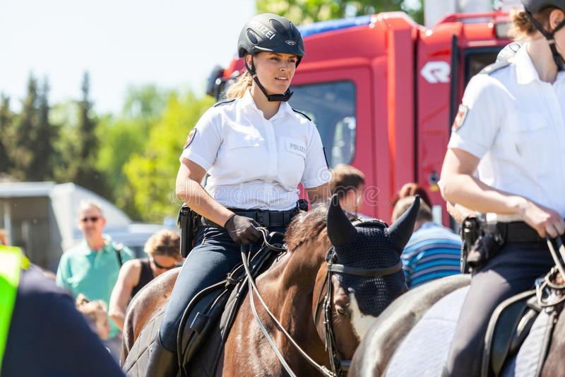 German police horsewoman rides on a police horse. DELMENHORST / GERMANY - MAY 6, 2018: German police horsewoman rides on a police horse for training exercise in royalty free stock images