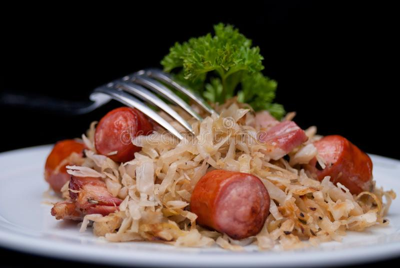 German, Polish, Austrian cuisine dish, Bigos - cabbage stewed with meat and sausages. On a white plate, beef, culinary, dinner, food, meal, mushroom, pork royalty free stock photo