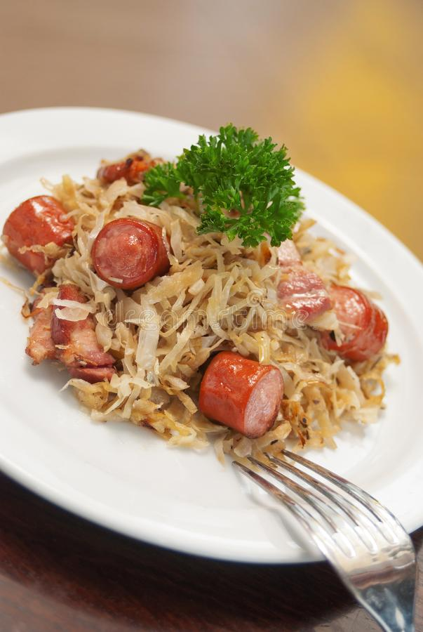 German, Polish, Austrian cuisine dish, Bigos - cabbage stewed with meat and sausages. On a white plate, beef, culinary, dinner, food, meal, mushroom, pork royalty free stock photography