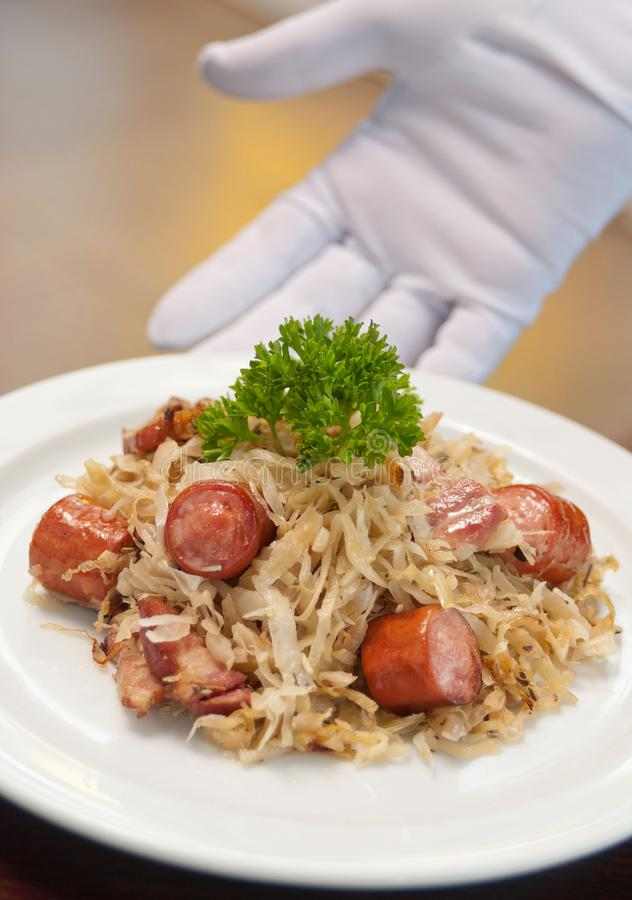 German, Polish, Austrian cuisine dish, Bigos - cabbage stewed with meat and sausages. On a white plate served, beef, culinary, dinner, food, meal, mushroom royalty free stock image
