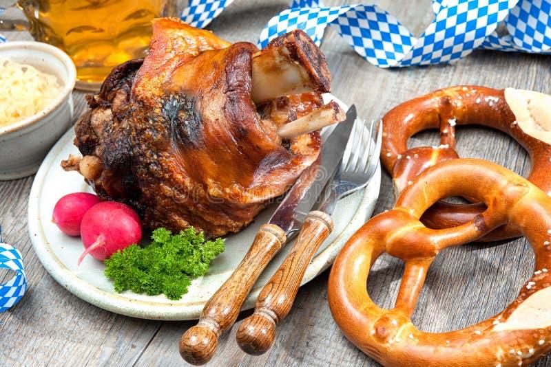 German Pork Knuckle. Schweinshaxe (German Pork Knuckle) with pickled cabbage and pretzel stock photography