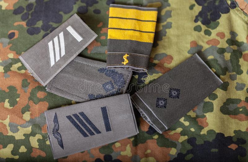 German shoulder ranks on a camouflage background. Shoulder ranks on a camouflage background stock photography