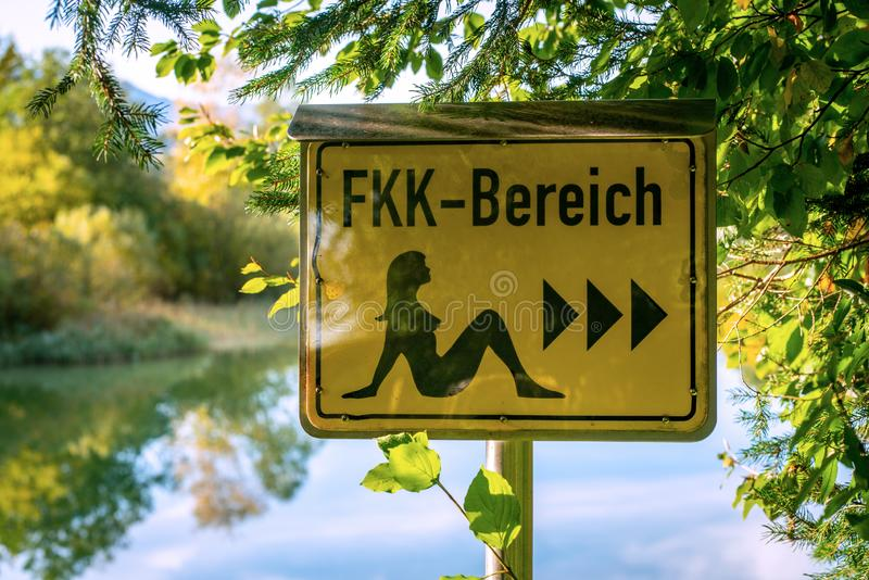 German sign board leading the way to the nude swimming area at the beach of lake Bibi in Bavaria stock image