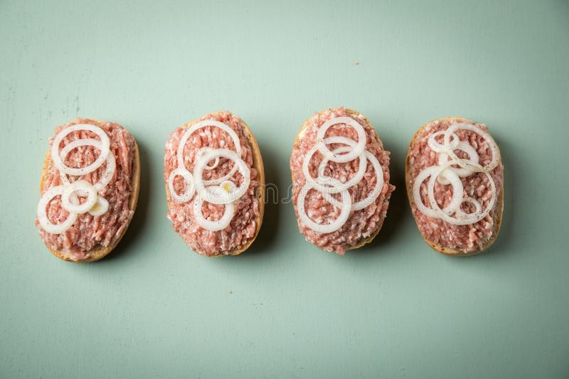 German snack bread roll buns with raw minced pork meat, butter, pepper and onion rings on mint green pastel background stock photos