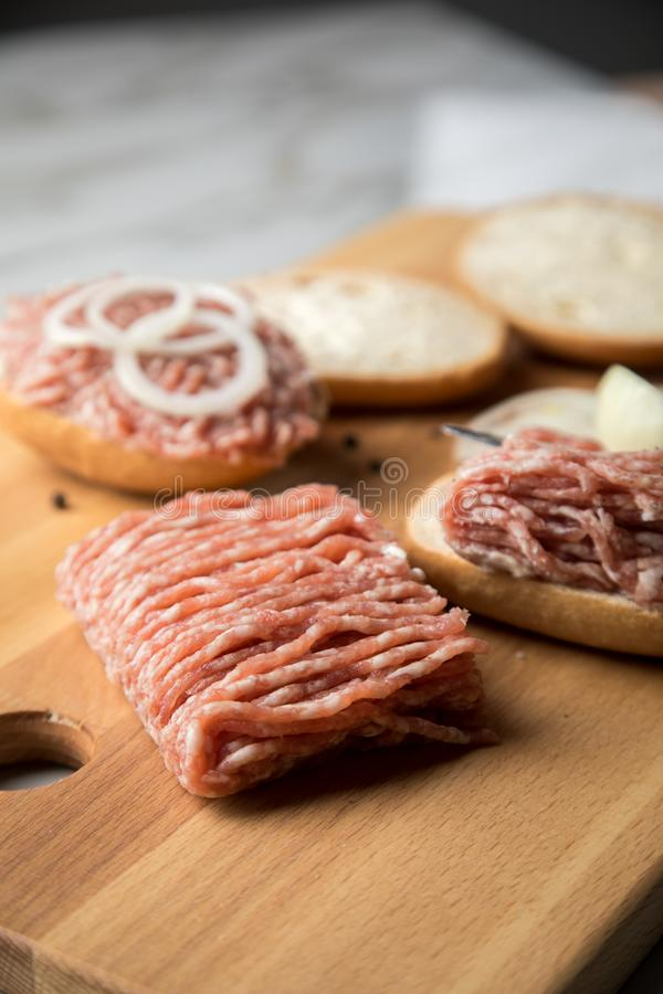 German snack bread roll buns with raw minced pork meat, butter, pepper and onion rings on wooden board and marble counter top royalty free stock photography