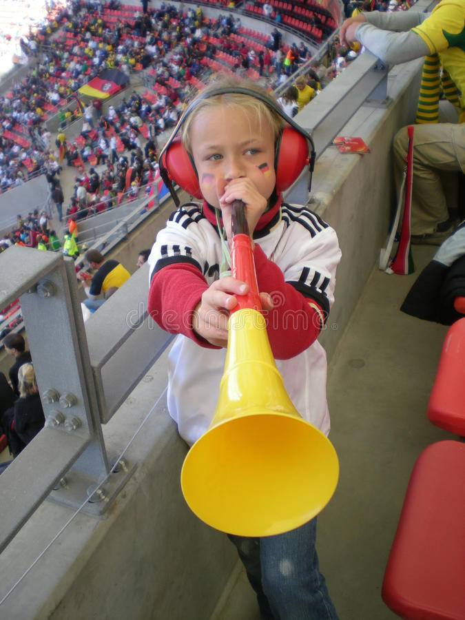 German soccer fan. A cute little Caucasian football fan girl dressed in German supporter clothes blowing her black, red and gold Vuvuzela horn in the stadium royalty free stock photography