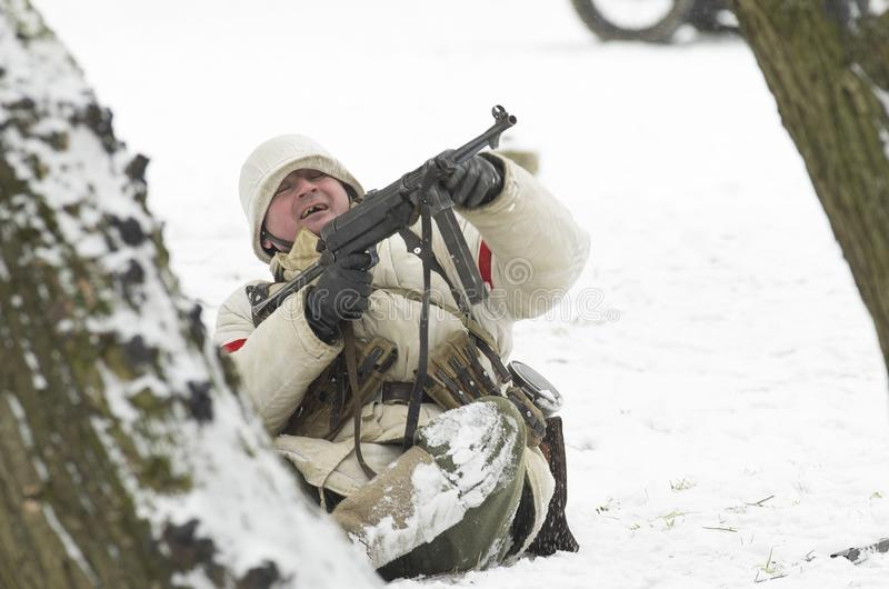 German soldier who is furiously shooting back from the submachine gun. St. Petersburg, Russia - February 23, 2017: German soldier who is furiously shooting back stock photography