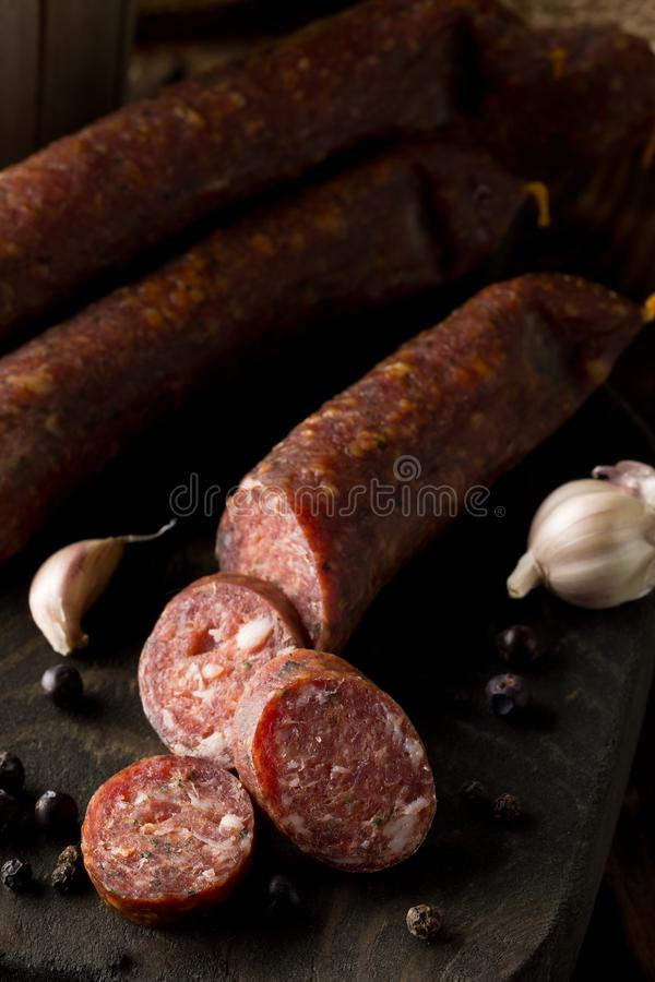German specialty salami hard cured sausage whole and cut with sp stock image