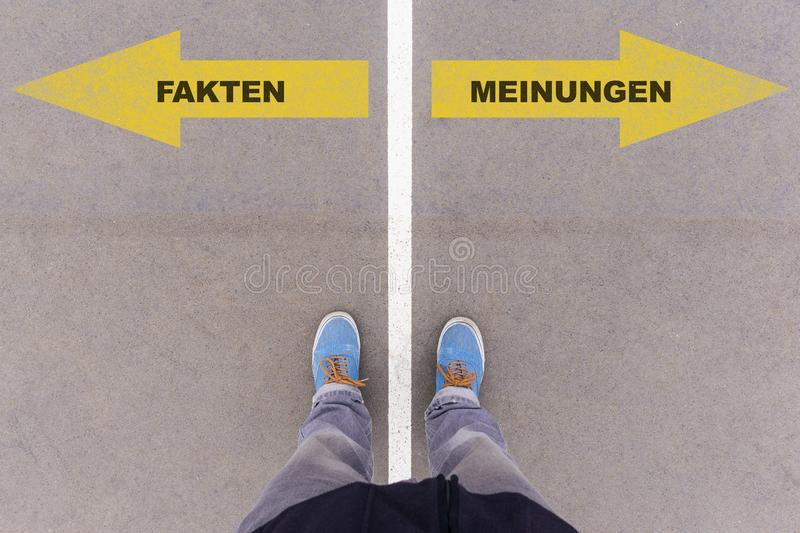 German text Fakten and Meinungen on asphalt ground, feet and shoes on floor. Fakten and Meinungen German for facts and opinions text on asphalt ground, feet and stock images