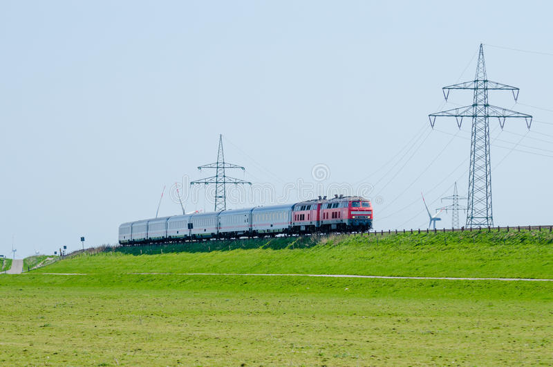 Download German Train Driving On Hindenburg Dam Towards The Island Sylt With Green Grass And Electricity Poles, Germany Stock Photo - Image: 83700071