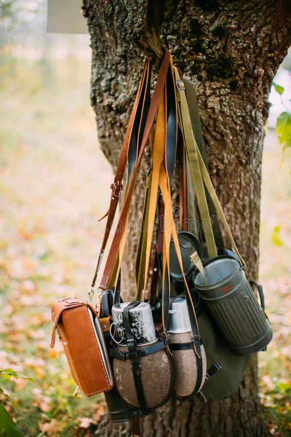 German Wehrmacht Infantry Soldier`s Military Equipment Of World. War II. Flasks And Bag Tank For Anti-gas Hanging In Tree Trunk stock photos