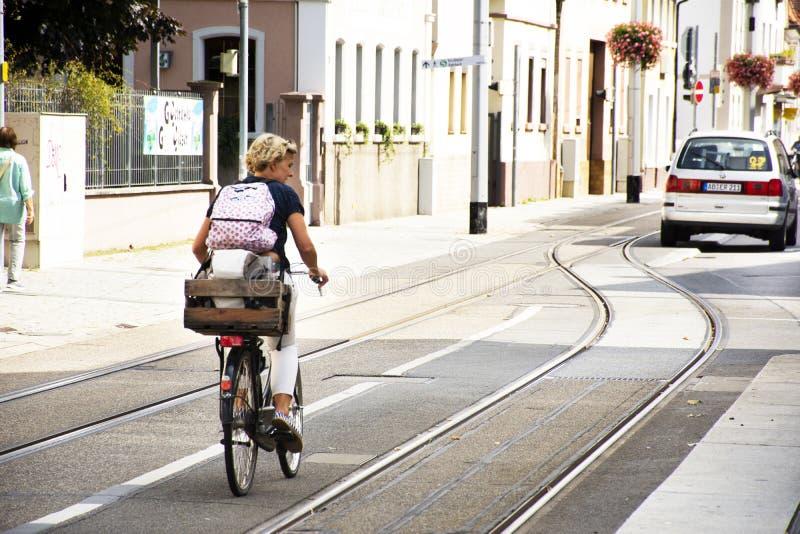 German woman people biking bicycle on Sandhausen street at Heidelberg-Kirchheim village in Heidelberg,. German woman people biking bicycle on Sandhausen street stock photos