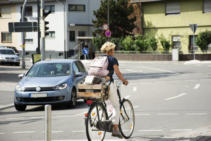 German woman people biking bicycle on Sandhausen street at Heidelberg-Kirchheim village in Heidelberg,. German woman people biking bicycle on Sandhausen street stock photography
