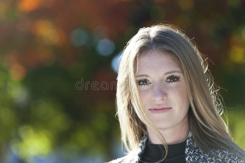 German woman smiling at the camera. Outside royalty free stock image