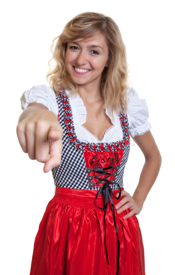 German woman in a traditional bavarian dirndl pointing at camera. On an isolated white background for cut out royalty free stock photo