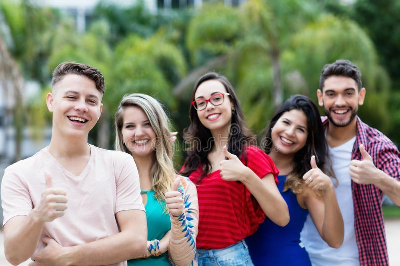 German young adult man with group of friends in line stock images