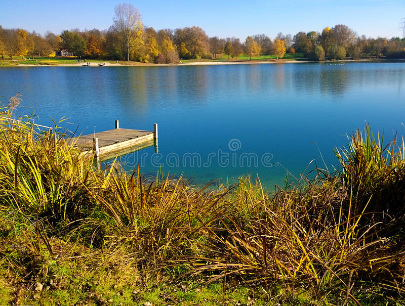 Germany, Bavaria - Erding lake on autumn with wooden pier. Germany, Bavaria - Idyllic view of Erding lake with blue waters, romantic wooden pier, trees with royalty free stock photos
