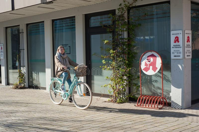 03/29/2019 Germany, the city of Kamen NRW young girl in the spring on a bicycle near the city pharmacy. Young girl in spring on a bicycle near the city pharmacy stock images