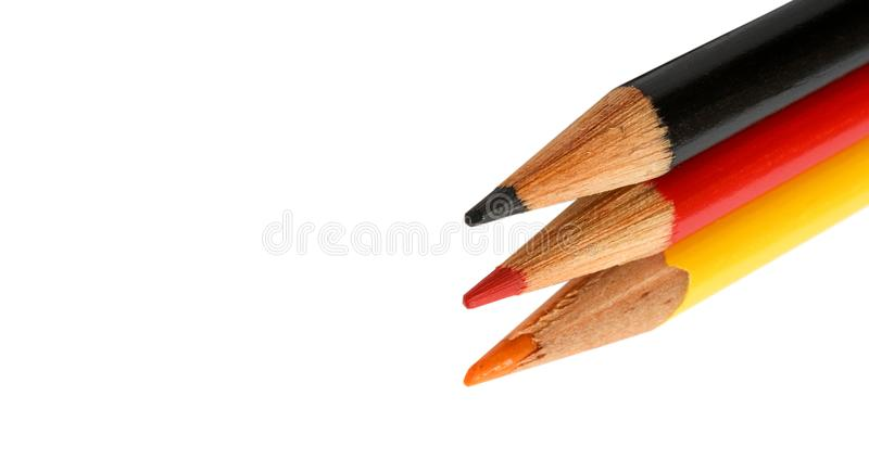 Germany flag colours in coloured pencils in black, red and gold on white background. Concept for German language, culture, people royalty free stock image