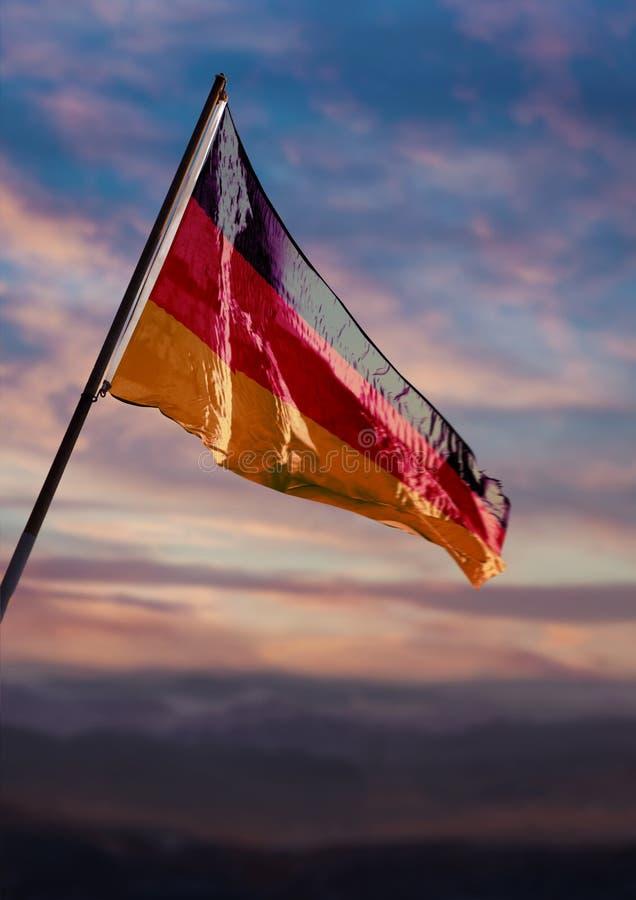 Germany flag, German flag waving on sky at dusk royalty free stock image