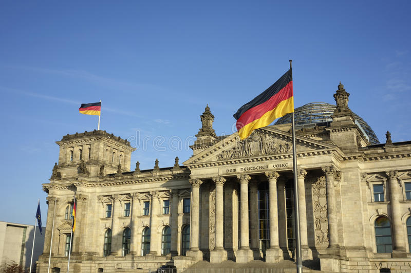 Germany Flag At Reichstag Building Berlin. Frontal view of Reichstag building with German flag waving in a beautiful day with blue sky, Berlin, Germany, Europe stock image