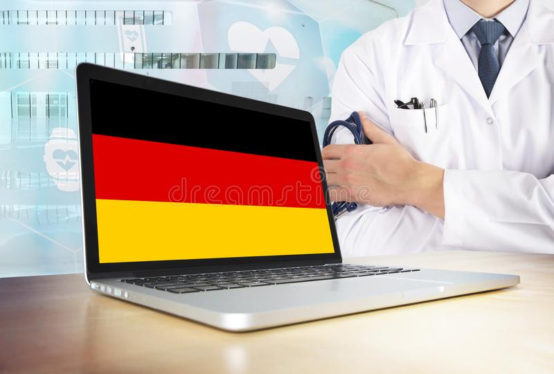Germany healthcare system in tech theme. German flag on computer screen. Doctor standing with stethoscope in hospital. Cryptocurrency and Blockchain concept stock photos