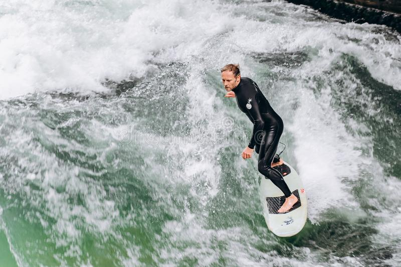 Germany, Munich - September 01, 2013. Atractive sporty man in neoprene shorty surfing on famous artificial river wave stock photography