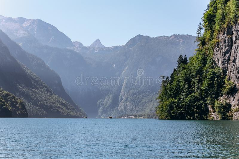 Germany, Munich - September 04, 2013. Snowy Mountains and Pine Tree Forest by Houses on a Lake in Bavaria stock photo