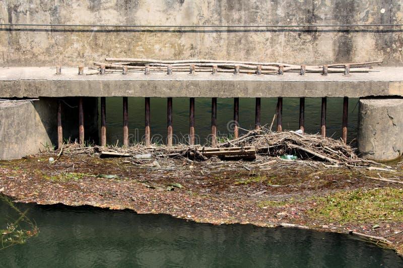 Geroeste metaalbars opgezet op concrete die dammuur wordt geplaatst om huisvuil te verhinderen drijvend op inkomend water stock fotografie