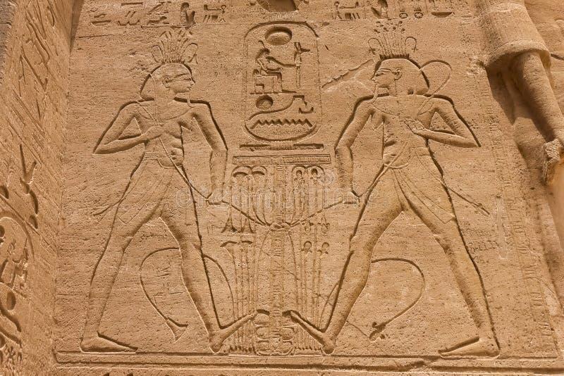 Geroglifici e disegni egiziani sulle pareti e sulle colonne Lingua egiziana, la vita dei antichi e la gente in geroglifico immagine stock libera da diritti