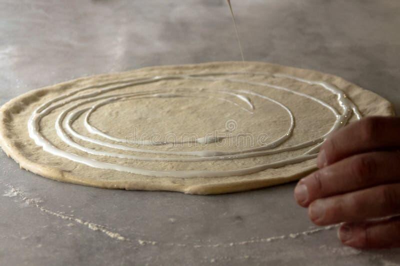 Gerold die pizzadeeg met room wordt bestrooid - een voorbereidingsproces stock afbeelding