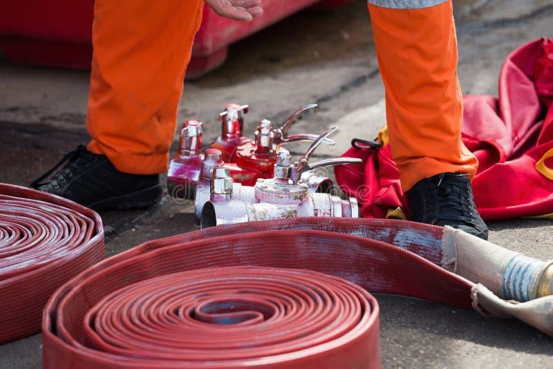 Gerold in een broodjes rode brandslang, de brandblusapparaten r van het Brandmateriaal stock afbeelding