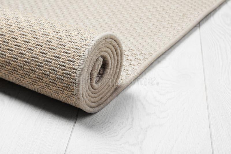 Gerolde geweven mat op houten achtergrond stock afbeelding