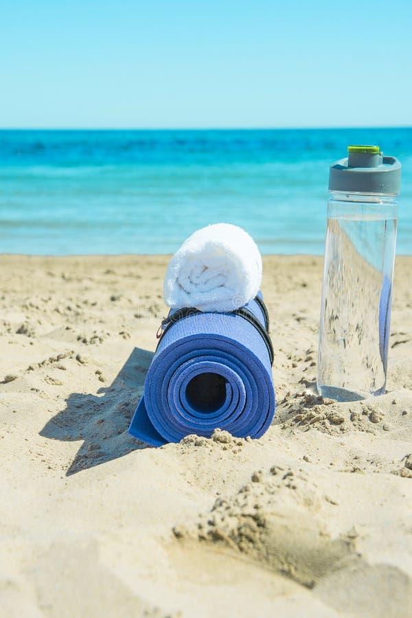 Gerolde Yoga Mat Bottle met Water Witte Handdoek op Strandzand met Turkooise Overzeese Blauwe Hemel op Achtergrond zonlicht stock foto