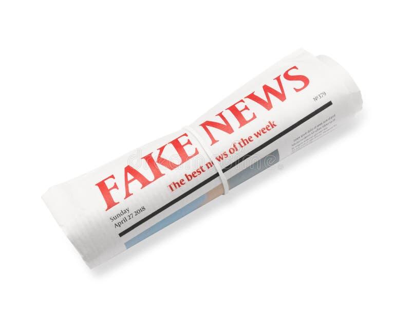 Gerollte Zeitung mit Schlagzeile GEFÄLSCHTEN NACHRICHTEN auf weißem Hintergrund stockfotos