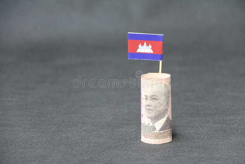 Gerolltes kambodschanisches Riel und Stock des Banknotengeldes fünfhundert mit Mini-Kambodscha-Flagge auf dunkelgrauem Boden und  stockfotografie