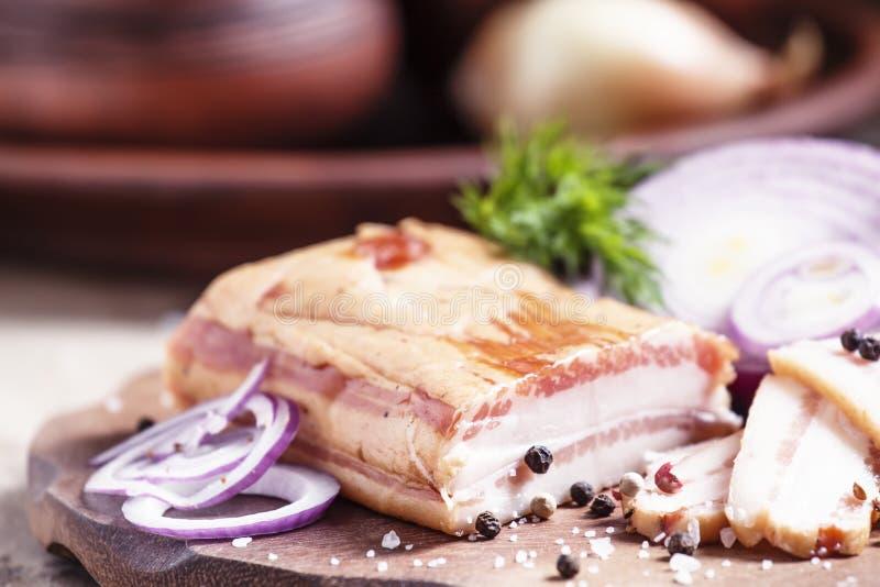 Gerookt bacon, rode ui, zout en peper op een kleischotel, nog l royalty-vrije stock foto's