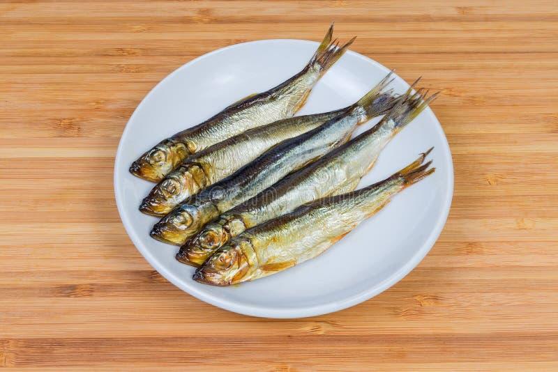 Gerookte Baltische haringen op de schotel stock foto's