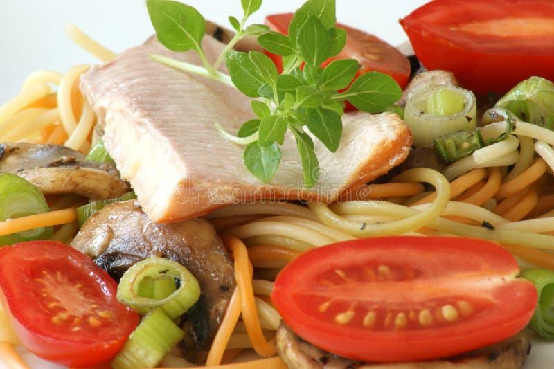Gerookte forel met gekleurde spaghetti en groente stock foto