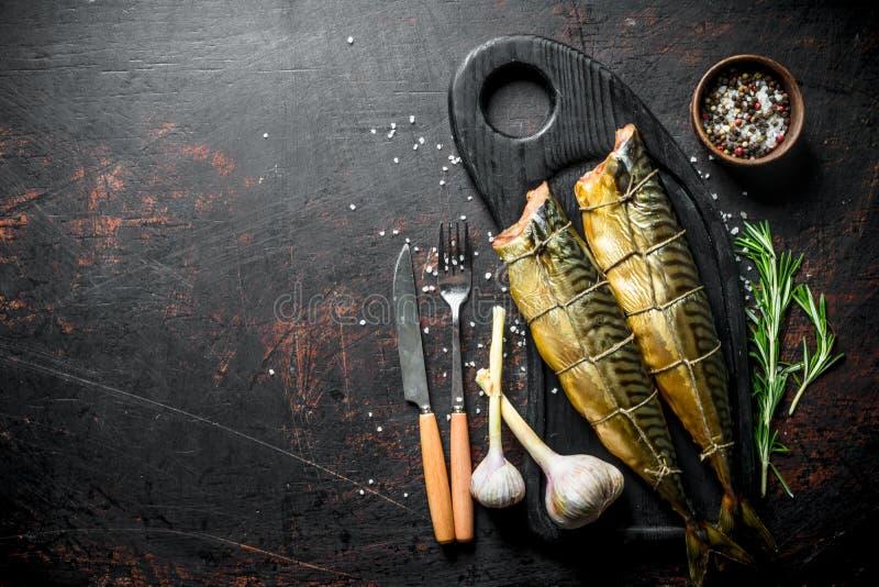 Gerookte makreel op een Hakbord met knoflook, rozemarijn en kruiden royalty-vrije stock foto