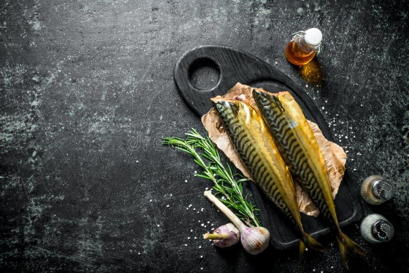 Gerookte makreel op een knipselraad met rozemarijn en knoflook royalty-vrije stock afbeeldingen