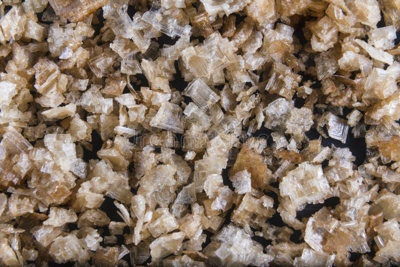 Gerookte overzeese zoute vlokken, op een houten lepel en verspreid. Macro. stock foto's