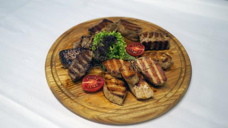Gerookte ribben op een grill met kip en saus stock afbeeldingen