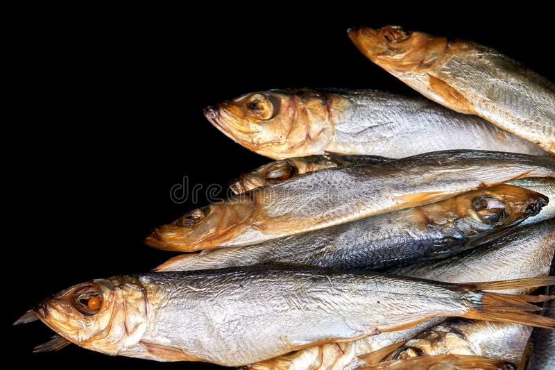 Gerookte vissen Baltische die haringen op zwarte achtergrond worden geïsoleerd stock afbeeldingen