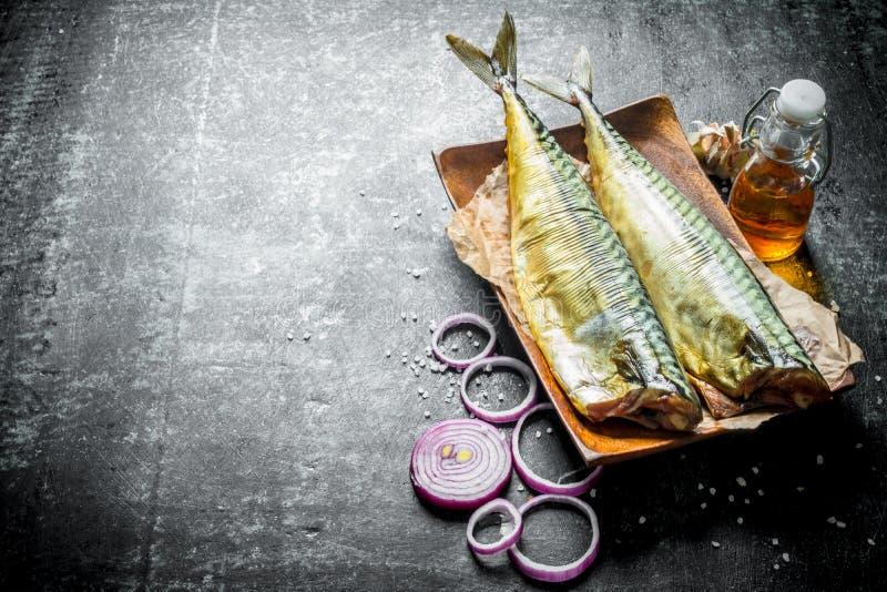 Gerookte vissenmakreel op een plaat met uiringen en knoflook stock afbeelding