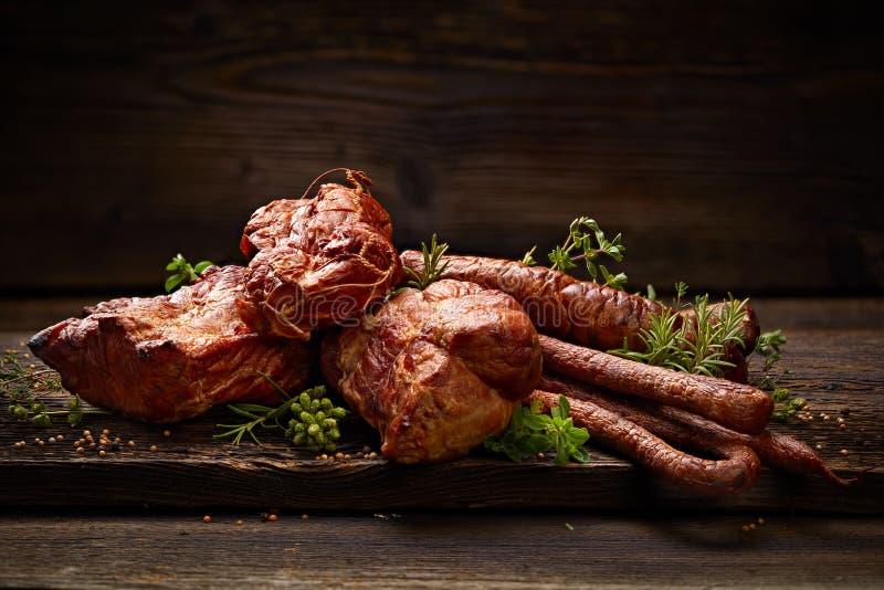 Gerookte vlees en worsten Een reeks traditionele gerookte vlees en worsten: ham, gerookte ham, varkensvleeslendestuk, huis-stijl  royalty-vrije stock foto