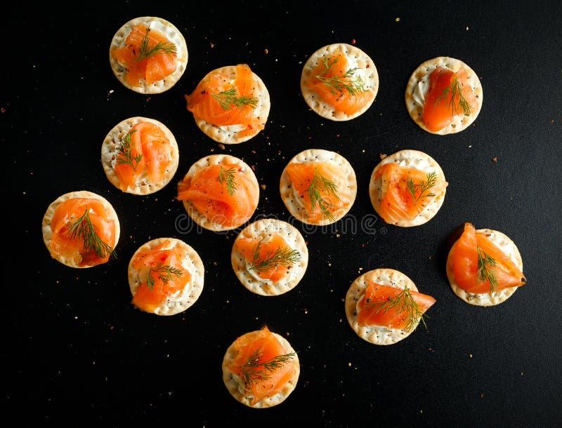 Gerookte Zalm en zachte chees canapes voorgerechten met bieslook op zwarte lijst stock fotografie