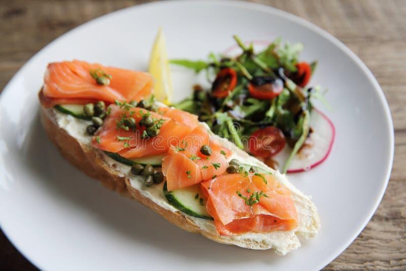 Gerookte zalm op geroosterd brood met verse room, citroen en salade royalty-vrije stock afbeeldingen