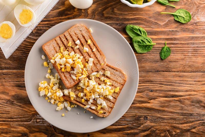 Geroosterd brood met besnoeiing gekookt ei op plaat stock afbeelding